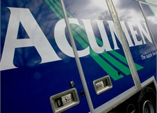 close up view of Acumen Logistics logo on the side of one of its covered car transport lorries