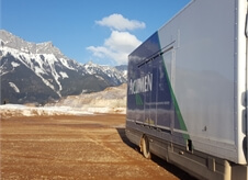 view down the side of an Acumen Logistics enclosed car transport lorry at the base of a picturesque mountain.