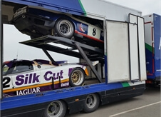 side view of an open covered car transport lorry showcasing two race cars within