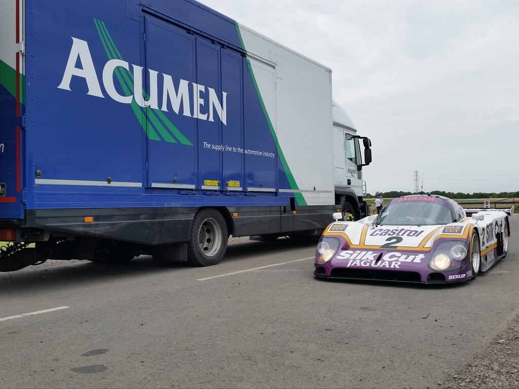 Acumen Logistics covered car transport lorry parked next to a race car that was delivered by the lorry.