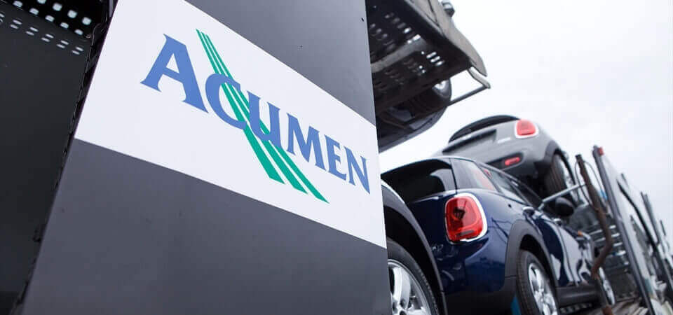 close up low angle shot of Acumen Logistics logo on a car transporter with mini's visible loaded on the car transporter in the background