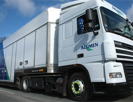 low angle shot of an Acumen Logistics covered car transporter.