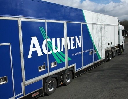 side view of an Acumen Logistics covered car transporter.
