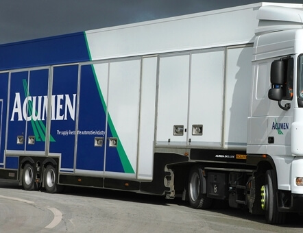 side view of an Acumen Logistics covered car transporter turning a sharp corner.