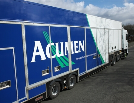 side view of an Acumen Logistics covered car transport lorry on a road