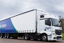 side view of an Acumen Logistics distribution lorry driving down a country side road