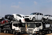 two Acumen Logistics car transporters parked next to each other with Range Rovers on one and Jaguars on the other.