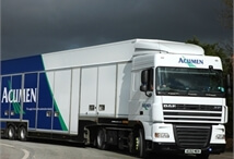 Acumen Logistics covered car transport lorry driving round a corner with overcast sky