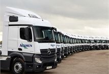 side view of a large number of new Acumen Logistics lorries all lined up in a slight curve