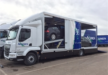 one of acumen enclosed car transporters with it's side open and 2 cars loaded on the lorry for covered car transport.