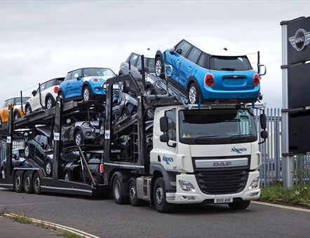 front view of an Acumen Logistics car transporter transporting a variety of colours mini's