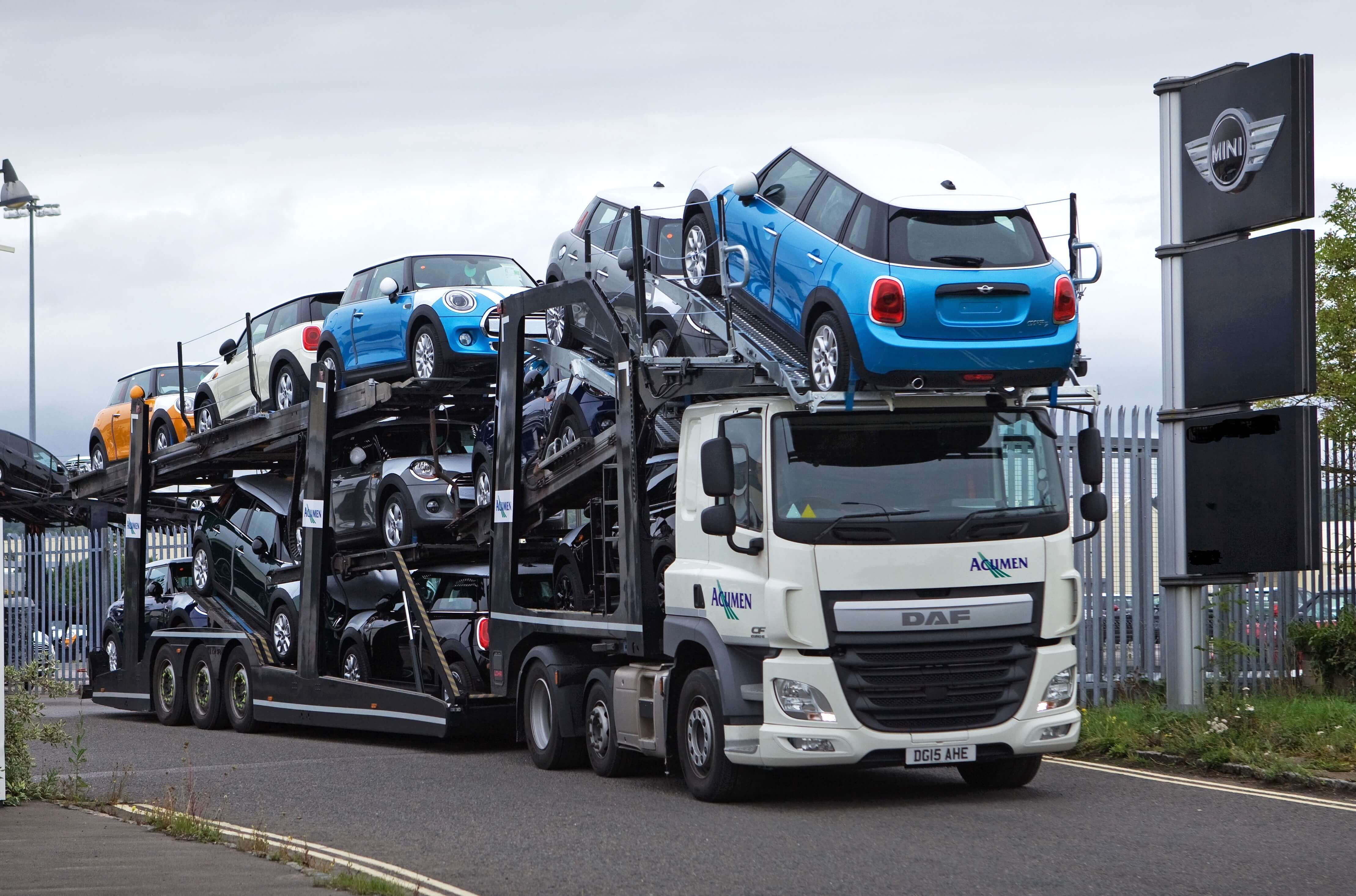 Front View Of An Acumen Logistics Car Transporter Transporting A Variety Of Colours Minis